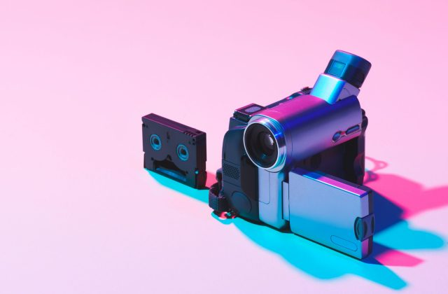 close up view of video cassette and digital video camera on pink background