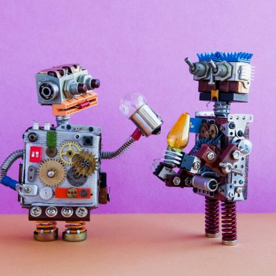 Robots communication, artificial intelligence concept. Two robotic characters with light bulbs. Creative design toys on pink wall, brown floor background